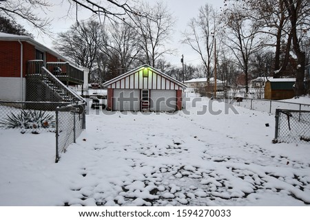 A house with a snowy driveway following a blizzard in Kansas City, Missouri. Picture taken in December around sunset.