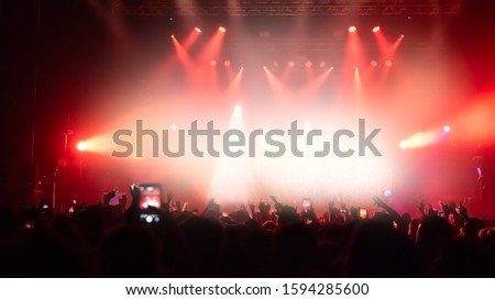 Silhouettes of concert crowd in front of bright stage lights. #1594285600