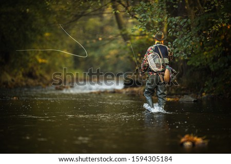 Close-up view of the hands of a fly fisherman holding a lovely trout while  fly fishing on a splendid mountain river Royalty-Free Stock Photo #1594305184