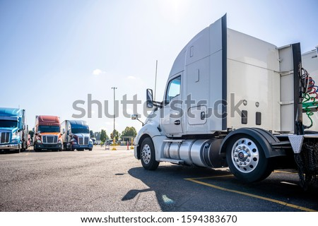 Long haul big rig white semi truck tractor stand on truck stop parking lot across another semi trucks standing in row for truck drivers rest waiting for the continuation of the cargo delivery route #1594383670