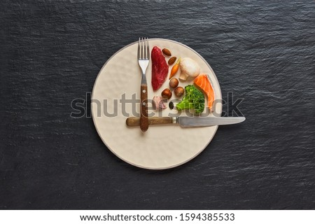20:4 fasting diet concept. One third plate with healthy food and two third plate is empty. Beef, salmon, egg, broccoli, tomato, nuts, carrots, mushrooms. Dark background. Top view. #1594385533