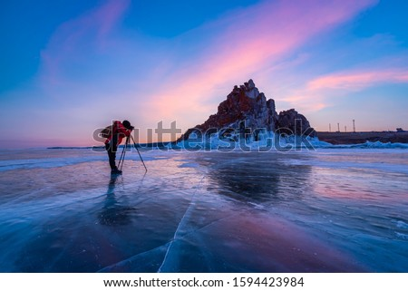 Photographer or Traveller using a professional DSLR camera take photo beautiful landscape of Baikal lake at sunset winter. The most tourist attraction in Rusia - Recreation and outdoor travel concept.