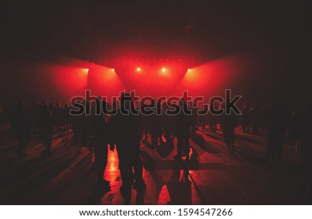 Concert crowd background.Group of young people on dance floor in music hall.Techno music party poster.Bright red stage lights in night club.Youth entertainment event in nightclub.