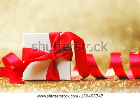 Christmas gift in white box with red ribbon decoration on golden background #159455747