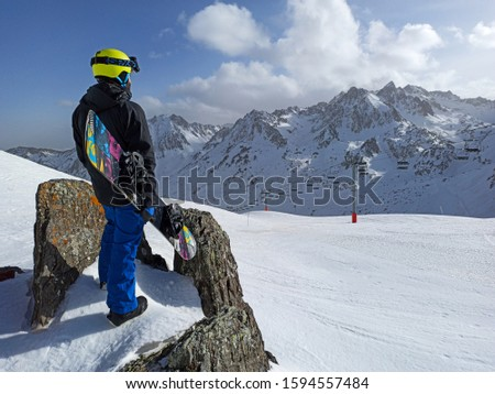 La Mongie, Pyrénées, France - Decembre 2019 - a snowboarder watching moutains and snow before ride for holidays in La Mongie.  #1594557484