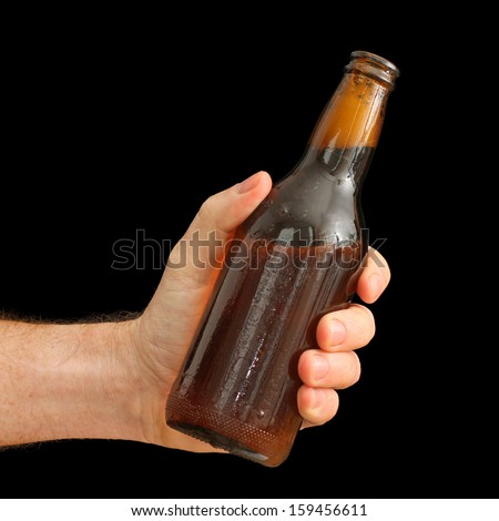 Man's Hand holding a Brown Bottle of Beer isolated on black #159456611