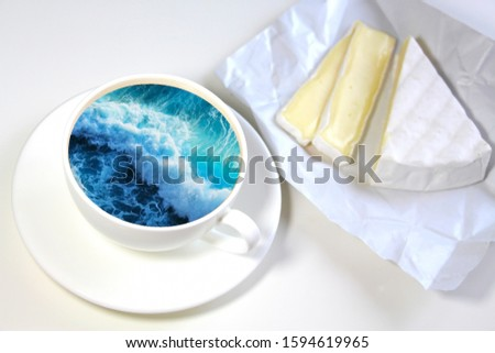 White cup with water. Sea. Ocean. Sea waves. Creative postcard. #1594619965