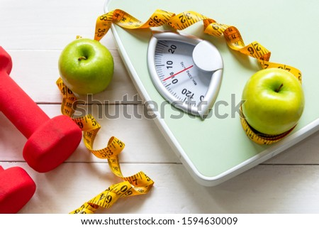 Diet and Healthy life loss weight Concept. Green apple and Weight scale measure tap with fresh vegetable and sport equipment for women diet slimming.  #1594630009