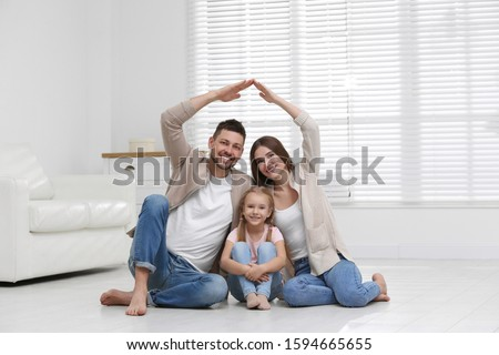 Happy family forming house roof with their hands at home. Insurance concept #1594665655