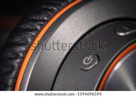A close up macro photo of the power button on a pair of generic headphones with curved lines #1594696594