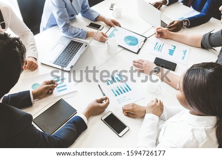 Documents, gadgets and hands of people on the desktop, top view. A team of young businessmen working and communicating together in an office. Corporate businessteam and manager in a meeting. Royalty-Free Stock Photo #1594726177