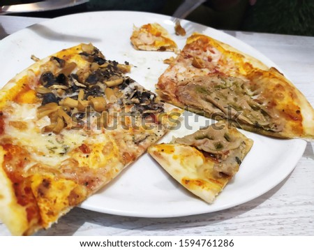 Fresh pizza slices with cheese, mushrooms and meat on the white plate on the wooden table background #1594761286
