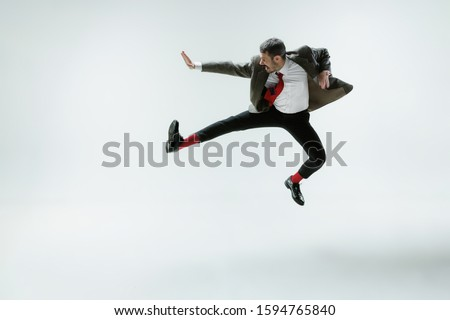 Young caucasian man moving flexible on white studio background. Male model in office attire bending over, avoiding something, catched in motion and action. Looks angry, scared, fighting. Emotions. #1594765840