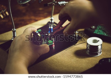 Hands of man holding solder iron  soldering the pin on electronics circuit board,  DIY hobbies and electrician workshop concept. #1594773865