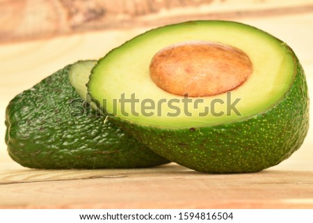 Two halves, cut across, green ripe avocado, with a stone. In the foreground is a half with a bone, in focus. In the background is the other part. Background of wood. #1594816504