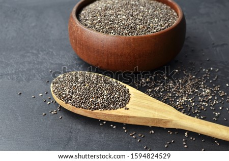 Raw organic chia seeds superfood in wooden bowl and spoon on dark stony background. #1594824529