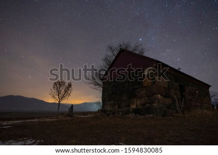 Beautiful night landscape. Small christian church at the night. A colorful star in the sky with an orientation to the northern star.  #1594830085