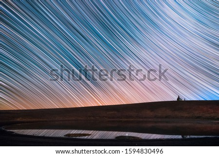Beautiful night landscape, small church and star trails reflected in the  lake. The colorful star trails on the sky. Night timelapse photography. #1594830496