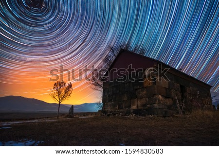Beautiful night landscape, small church and star trails. The colorful star trails on the sky with orientation on the north star. Night time lapse photography. #1594830583