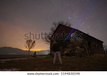 Beautiful night landscape, a girl with a flashlight stands at a small church. A colorful star in the sky with an orientation to the northern star.  #1594830598