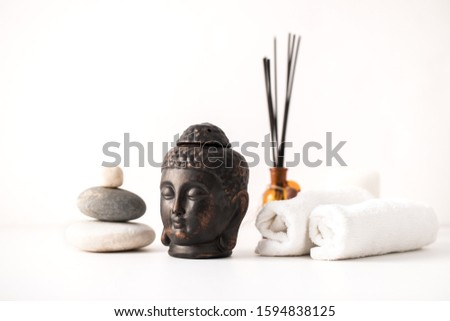 Clay buddha head aroma lamp, aroma sticks, stone composition and spa towels – spa composition on white background #1594838125
