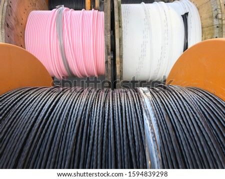 Close up of black fiber optic cable on roll. White and pink cables on rolls. High speed internet and communication. Part of a serie. #1594839298