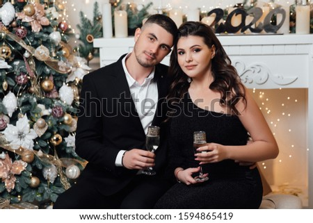 Turned photo of two people romantic man feel romance enjoy christmas time holidays in house with newyear decoration indoors.  Couple in love holding champagne glasses. Christmas time.  #1594865419