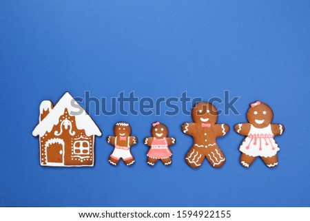 The hand-made eatable gingerbread house, little men on blue background #1594922155