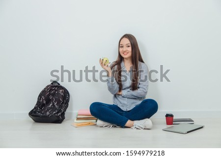 Lovely smiling asian student girl sitting on the floor in lotos position, holding an apple. A lot of school supplies around her. #1594979218