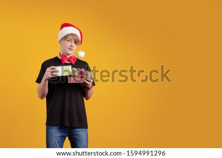 Young guy in a red Santa Claus hat holds in his hands banknotes, money and posing on a yellow background #1594991296