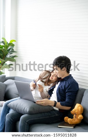 Couple shopping online with credit card and using laptop computer at home. #1595011828