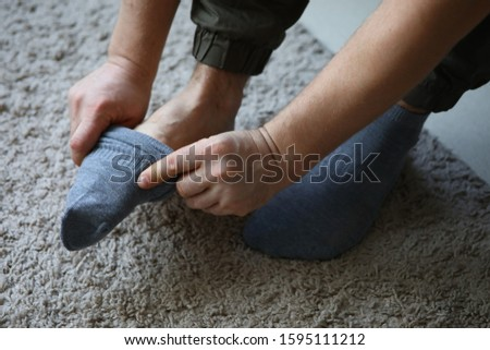 Man at home in morning puts gray socks on his leg. For a long time do not change clothes concept #1595111212