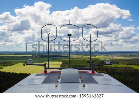 Measurement devices (cup anemometer, ultrasonic anemometer, wind vane) and aviation lights on the nacelle roof of a wind turbine with fields and cloudy sky in the background #1595162827