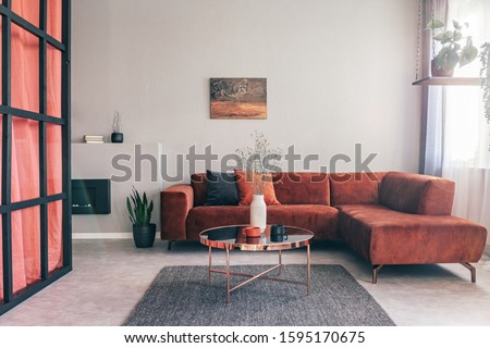 Real photo of a simple, elegant living room interior with red furniture and an oil painting on white wall #1595170675