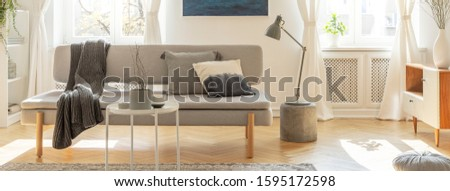 Grey lamp on small table next to comfortable sofa with pillows #1595172598