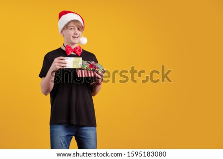 Young guy in a red Santa Claus hat holds in his hands banknotes, money and posing on a yellow background #1595183080