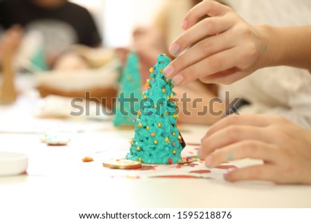 Children's hands decorate the gingerbread Christmas tree  #1595218876