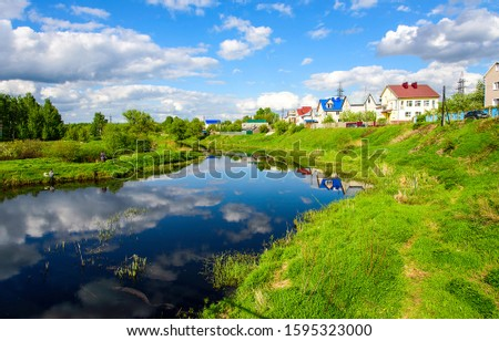 Summer village river landscape. Summer river in village. River in summer village. River village houses view #1595323000