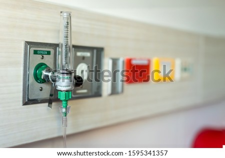 Oxygen flow meter plugged in the green outlet on hospital wall, Medical equipment. Oxygen for patients in the wall. Oxygen Gas Pipeline connection Inside Hospital ICU Room.