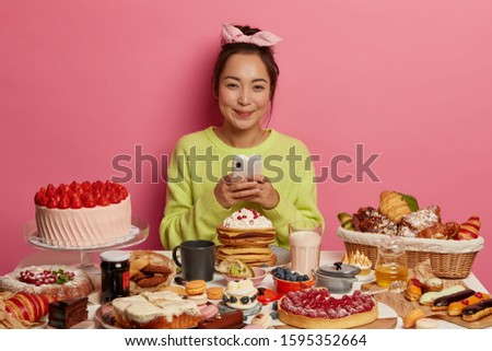 Calories, appetite and dieting concept. Satisfied Asian girl has tasty snack, sugar addiction, assortment of unhealthy products on table bad for figure and teeth, enjoys treat, uses cellular #1595352664