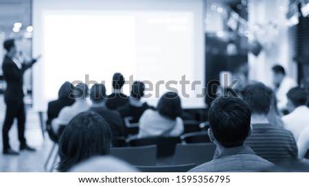 Seminar with expert speaker presenting to audience in hall. Blank business presentation screen for copy space. Executive presenter giving a speech. Leadership training coach in workshop lecture. #1595356795