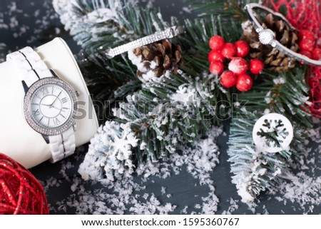 White wristwatch with Swarovski Crystals on a pillow and diamond bangles next to Christmas decorations. Christmas composition. #1595360767