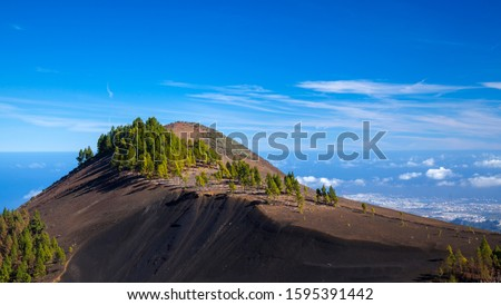Gran Canaria, December, dark volcanic ash moutain Montanon Negro, ie Black Mountain, Las Palmas in far distance Royalty-Free Stock Photo #1595391442