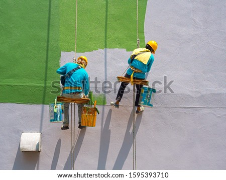 Two painters are painting the exterior of the building on a dangerous looking scaffolding hanging from a tall building. #1595393710