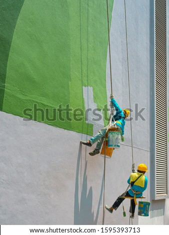 Two painters are painting the exterior of the building on a dangerous looking scaffolding hanging from a tall building with copy space. #1595393713