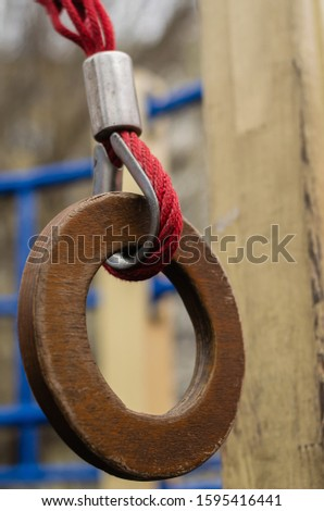Gymnastic ring on the playground outdoors. Closeup of a wooden gymnastic ring on a red rope. Selective focus. The vertical location of the picture.