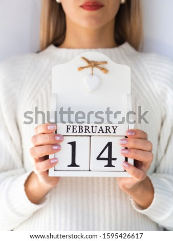 Valentine's day for singles. A pretty single woman holds wooden block calendar 14 February date #1595426617