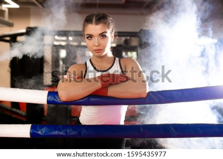 confident caucasian female boxer in sportive wear in ring, love boxing, box is her hobby. Professional boxer woman wearing red protective bandages on hands #1595435977