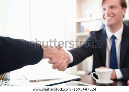 Selective focus of executive businessman is having handshake and smiling toward his partner with happiness and confident, successful business agreement, corporate partnership,teamwork and partnership. #1595447524