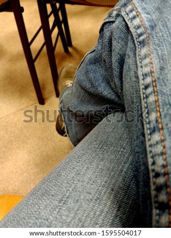 Lady's elegant long legs in jeans in a sitting position leg-on-leg #1595504017
